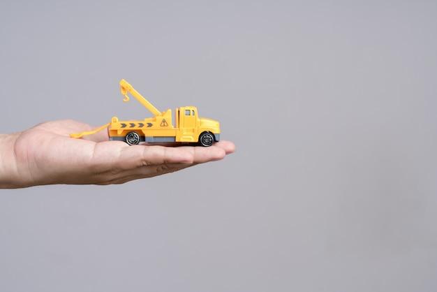 緊急のレッカー車のおもちゃの車を持っている手 Premium写真