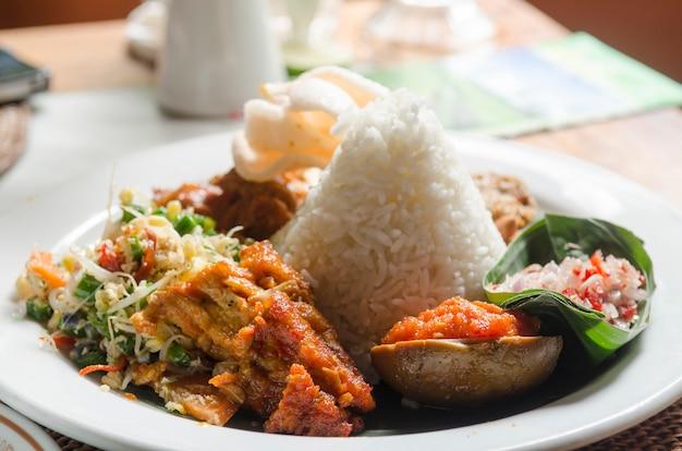 インドネシアで人気のナシレマック風料理新鮮な野菜ナッツと魚の米 Premium写真