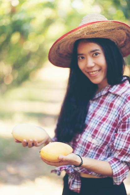 有機農場でマンゴー果実を選ぶ若いアジア農家 Premium写真
