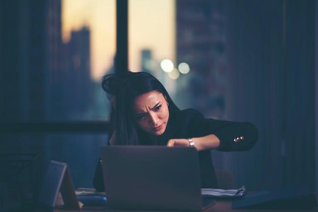 彼女の時計を見てホームオフィスで疲れた女性 Premium写真