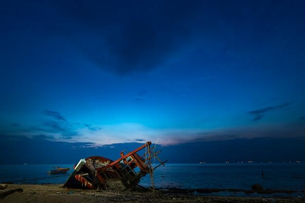 漁船のビーチで沈没船、夕日 Premium写真