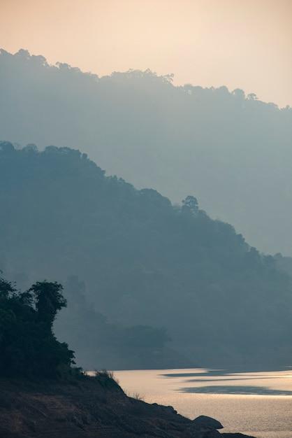 Горные слои с озером, фон тропический лес Premium Фотографии
