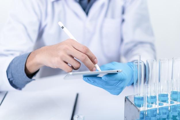 実験室の研究者化学物質と顕微鏡で勉強する Premium写真