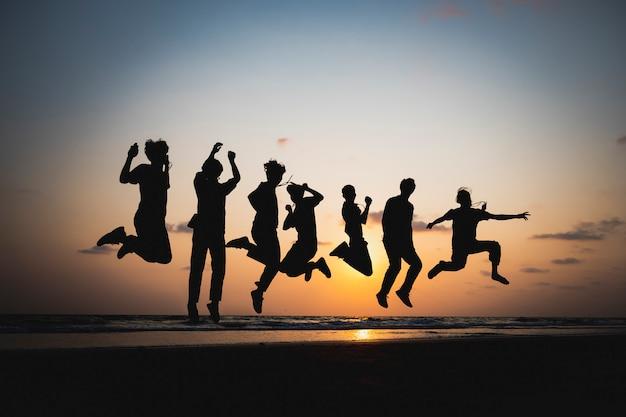 夕暮れ時、海でジャンプする友人のシルエット Premium写真