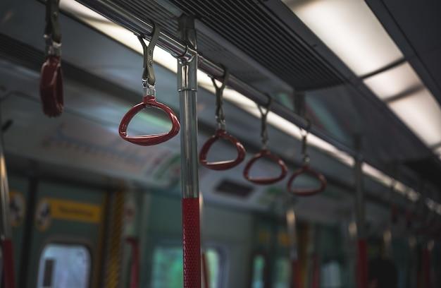 Изображение руки держало внутри поезда метро без пассажиров. Premium Фотографии