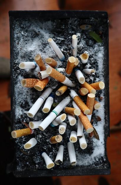 Сигареты затем оставляют в пепельнице в месте для курения. Premium Фотографии