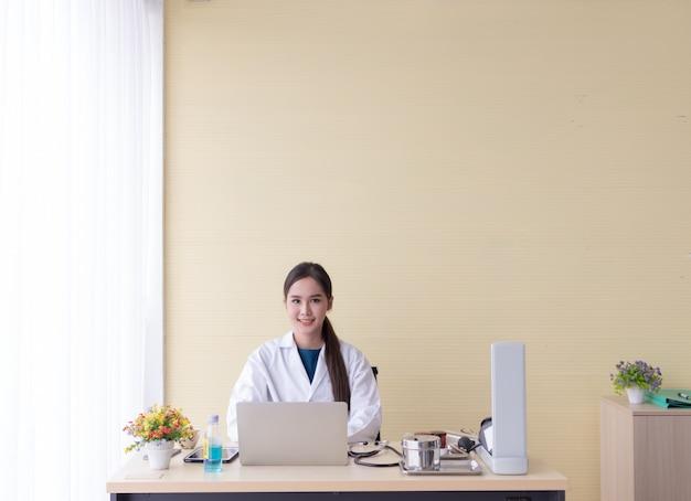 Азиатская женщина-врач сидела за компьютером и счастливо улыбалась. Premium Фотографии
