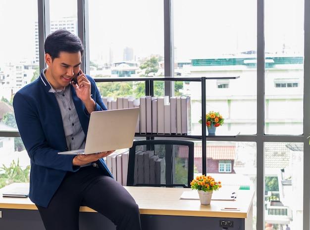 Молодой азиатский бизнесмен с ноутбуком и улыбкой в офисе Premium Фотографии