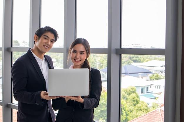 若いアジア人ビジネスマンとビジネスウーマンが一緒に仕事を相談します。職場でノートブックを見る Premium写真