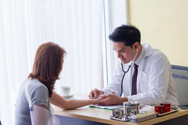 Мужской азиатский врач проверил пульс пациента, чтобы проверить аномалии сердца на столе Premium Фотографии