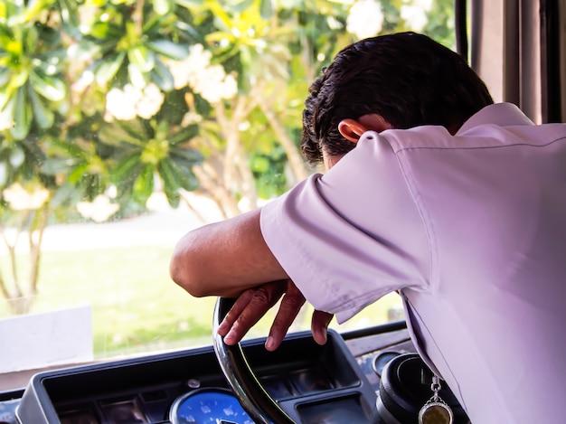Водитель автобуса, одетый в белую рубашку, заснул на рулевом колесе автобуса Premium Фотографии