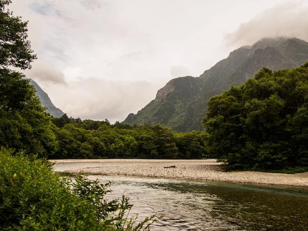 上高地の雲を背景にした山の森を流れる川の眺め Premium写真