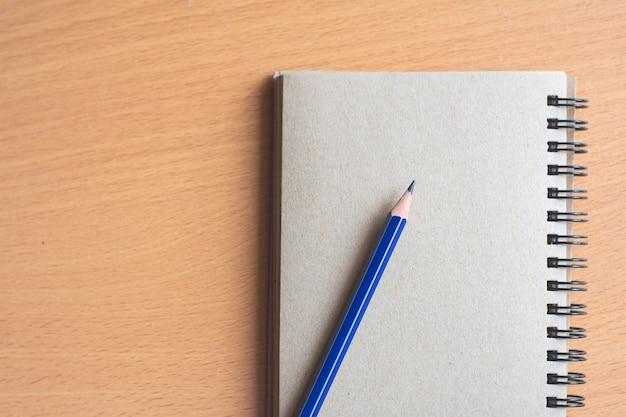 木板の背景に鉛筆でメモ帳。教育、ビジネス写真の壁紙を使用します。紙と概念、オブジェクトまたはコピースペースが付いている本の製品のメモを取ります。 Premium写真