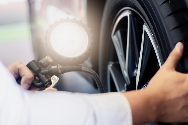 アジア人の車の検査量を測定膨らませたゴムタイヤ車。クローズアップハンドホールディングマシン Premium写真