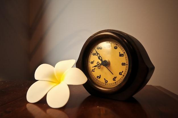 プルメリアの花とテーブルの上のヴィンテージの木製のタイの卓上時計 Premium写真