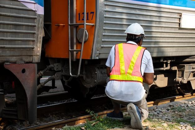 チェック電車で安全ヘルメットを身に着けているエンジニア Premium写真
