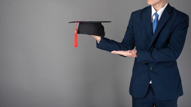 ビジネスマンは、卒業帽子、ビジネス教育の概念を保持している Premium写真
