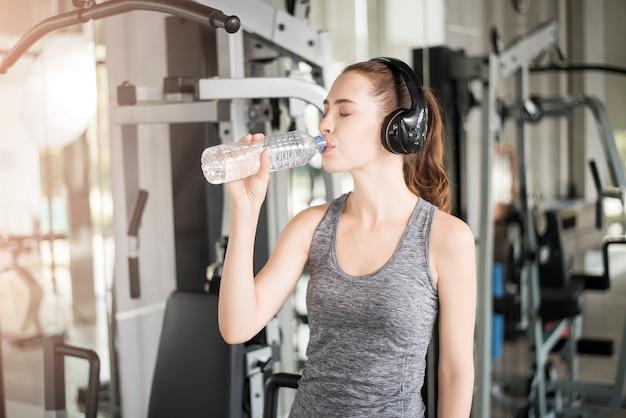 かなり若いスポーツ女性はジム、健康的なライフスタイルで水を飲む Premium写真