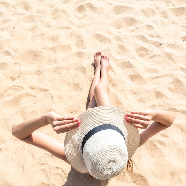 美しい女性はビーチに座っています。 Premium写真