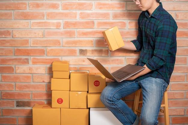 男性起業家の所有者中小企業のビジネスは彼の顧客を送るための梱包箱です。 Premium写真