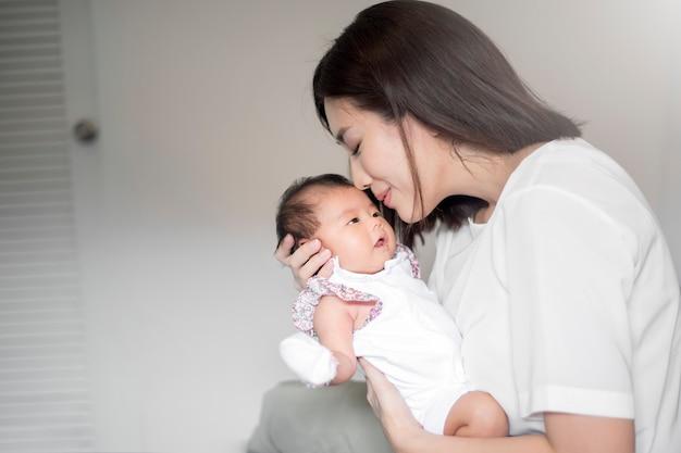 彼女の腕の中で生まれたばかりの赤ちゃんを持つ美しい女性 Premium写真