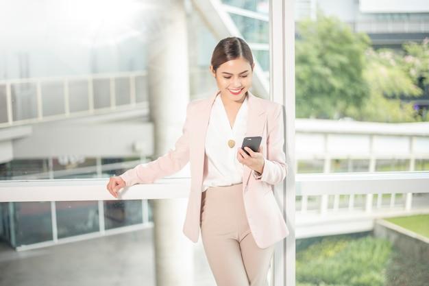 美しいビジネス女性がビジネスにスマートフォンを使用しています Premium写真