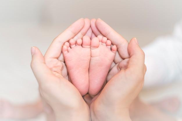 Крупным планом новорожденного ребенка ноги на женских руках Premium Фотографии