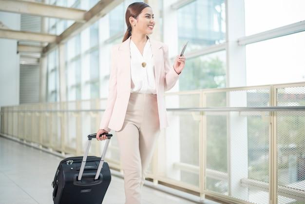 Красивая деловая женщина гуляет в аэропорту Premium Фотографии