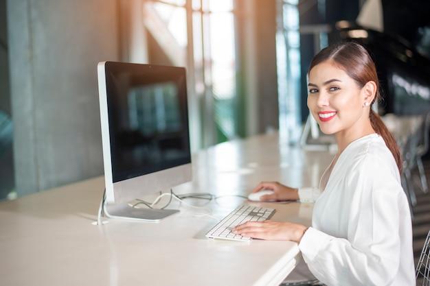 美しいビジネス女性は彼女のコンピューターで働いています。 Premium写真