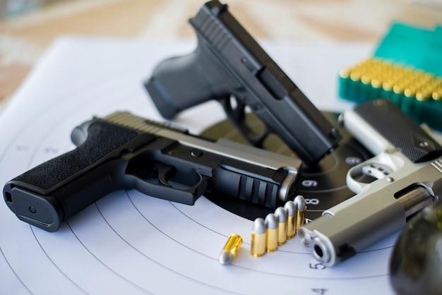 Пистолеты с боеприпасами на бумаге стреляют по мишеням Premium Фотографии