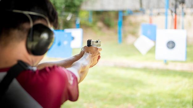 Мужчина практикует стрелять из пистолета Premium Фотографии