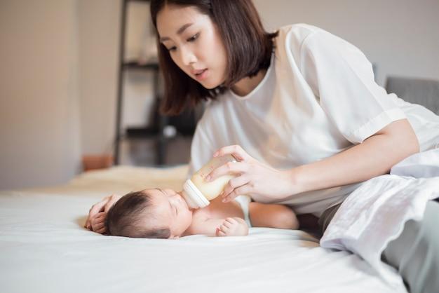 生まれたばかりの赤ちゃんの女の子は彼女の母親によって牛乳を飲んでいます。 Premium写真