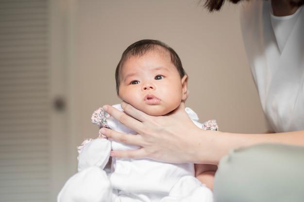 生まれたばかりの赤ちゃんの女の子は、牛乳を飲んだ後ママによって彼女の背中に触れて Premium写真