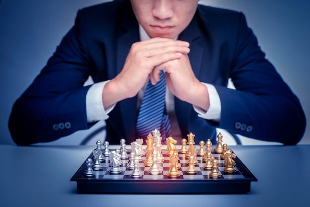 ビジネスの男性はチェス、経営戦略の概念を果たしています。 Premium写真