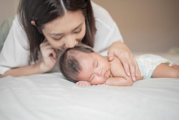 美しい母親は寝室で彼女の生まれたばかりの赤ちゃんと遊んでいます。 Premium写真