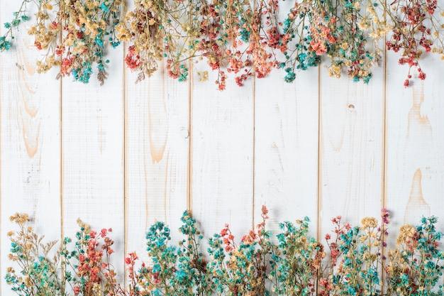 白い木製の背景に結婚式の花のトップビュー Premium写真