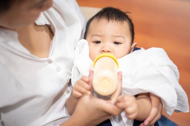 生まれたばかりのかわいい赤ちゃんはママによってボトルからミルクを飲んでいます。 Premium写真
