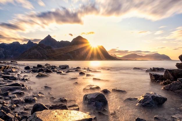 Прекрасный вид на горы и пляж на лофотенских островах на закате Premium Фотографии