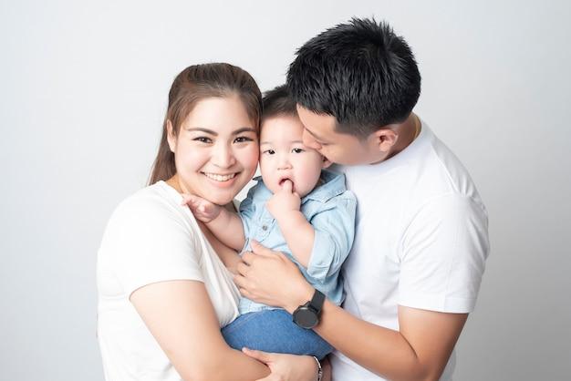 幸せなアジアの家族はスタジオで息子と一緒に楽しんでいます Premium写真