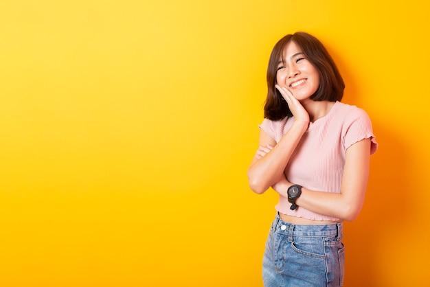 黄色の壁に満足して美しいアジアの女性大学生 Premium写真