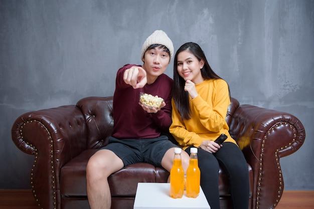 Счастливая пара сидит дома и смотрит фильмы Premium Фотографии