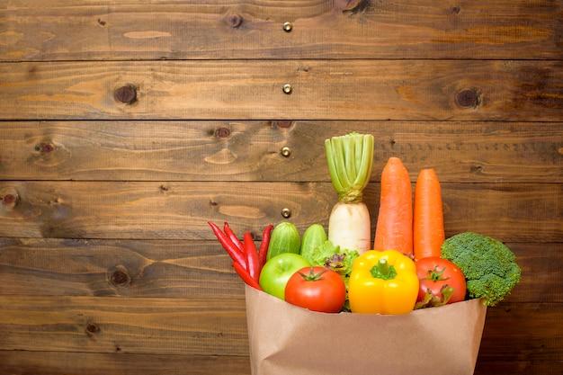 Овощи в продуктовой сумке на фоне дерева Premium Фотографии