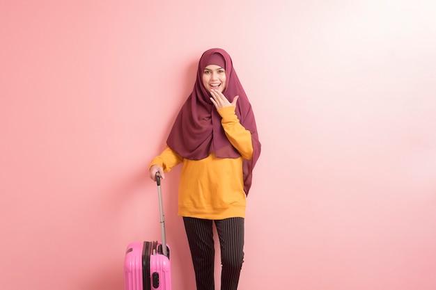ヒジャーブとイスラム教徒の女性がピンクの背景に荷物を持っている、人々旅行の概念 Premium写真