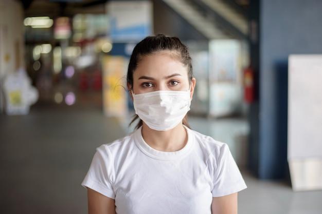 屋外に立っているマスクを持つ若い女 Premium写真