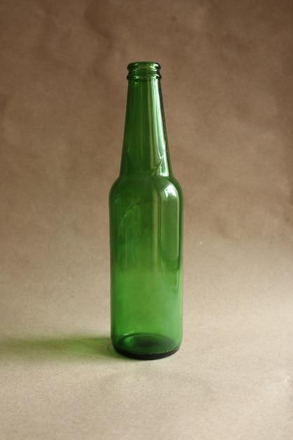 茶色の背景に緑色のビール瓶 Premium写真