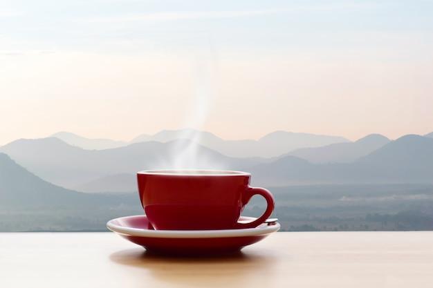 朝の太陽の光の山の景色と赤のコーヒーカップ Premium写真