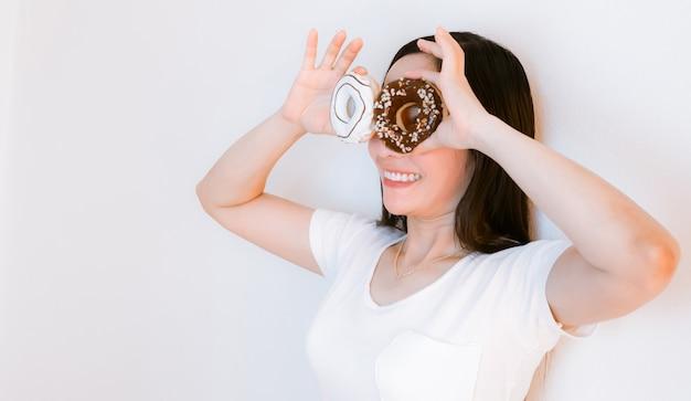Женщины азии в белых рубашках держат пончики для еды Premium Фотографии