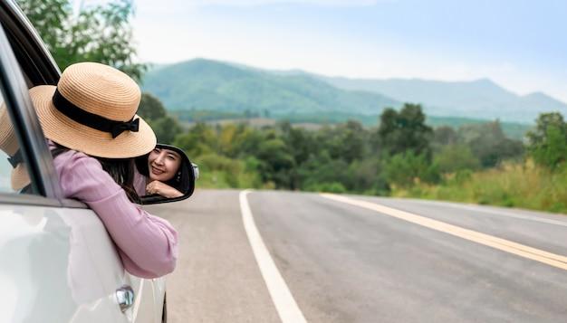 道路上の運転の女性が車で旅行をリラックスします。 Premium写真