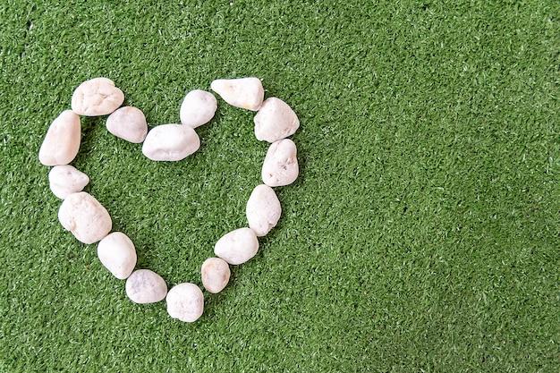 白い石は愛のための草の緑の背景にハート型 Premium写真