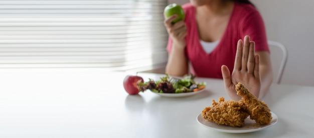 Панорамный баннер. диета. молодая красивая женщина отказывается от жареной курицы, нездоровой пищи или нездоровой пищи и ест свежий салат из зеленого яблока для хорошего здоровья дома Premium Фотографии
